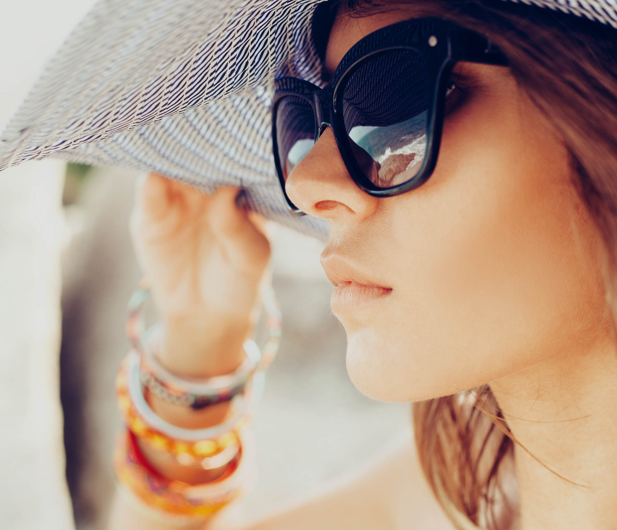 Lady wearing sunglasses and wide brimmed sun hat