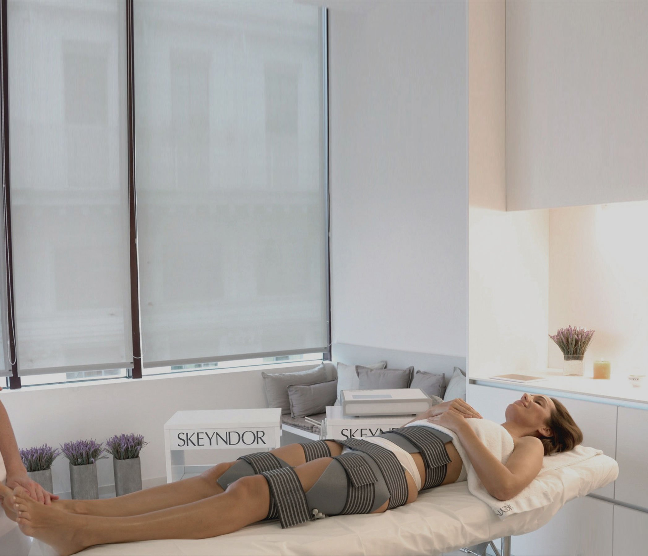 Lady lying on salon bed wrapped in slim drone treatment pads