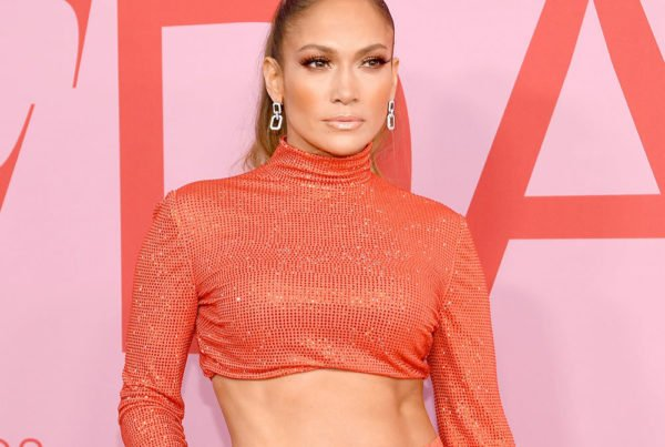 Jennifer Lopez wearing sparkly orange outfit showing abs